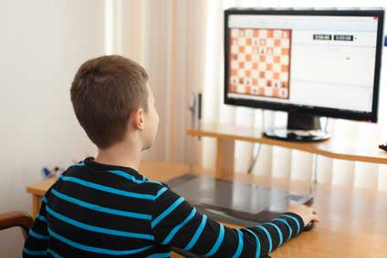 kid playing chess on computer